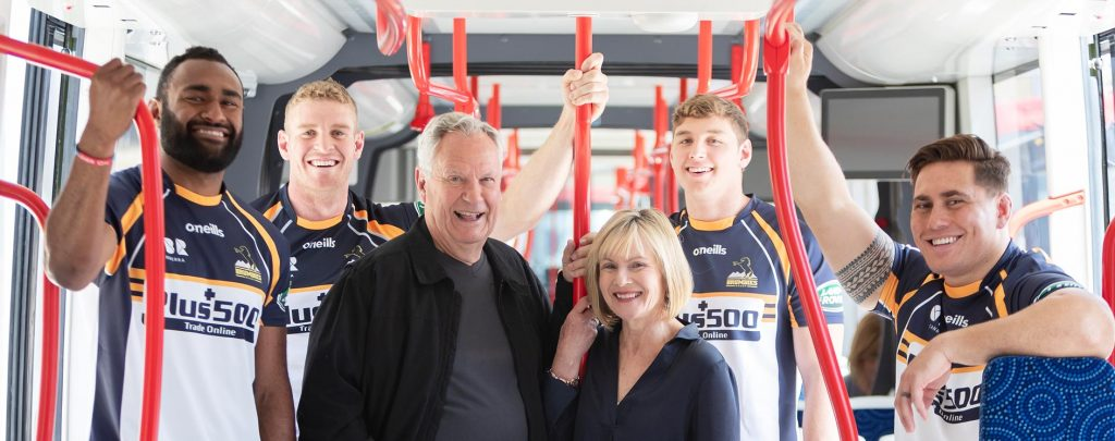 Brumbies players riding a Canberra Metro light rail vehicle with happy middle-aged couple
