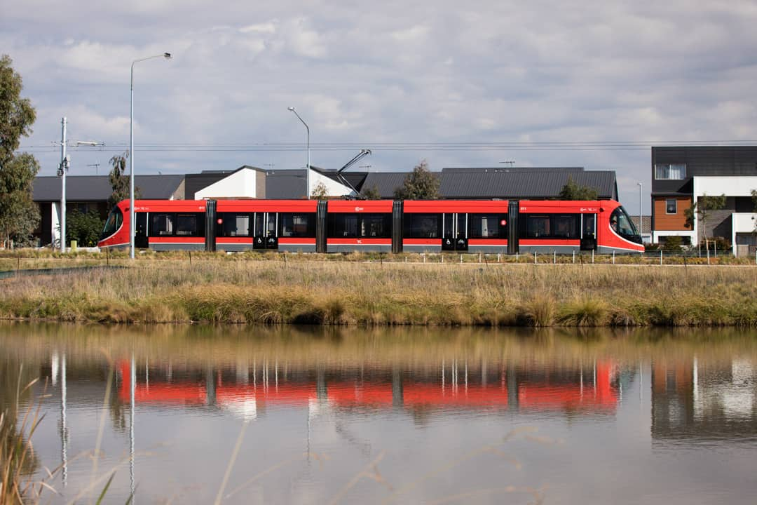 Side on shot of light rail vehicle going past stream in the Gungahlin area